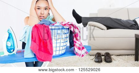 Woman fed up with ironing against low section of a businessman resting on sofa in living room