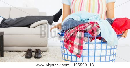 Full laundry basket against low section of a businessman resting on sofa in living room