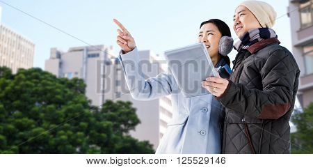 Couple looking away while holding digital tablet against low angle view of city buildings