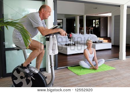 Portrait of a senior man making exercise bike and a senior woman doing yoga