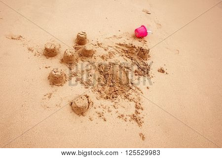 Child`s Sand Castles on a Beach or in Sandbox with Little Pink Plastic Bucket