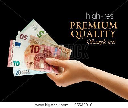 Woman's hand holding money isolated on black background. Business concept