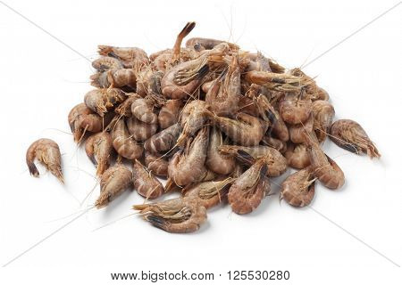 Heap of unpeeled brown shrimps on white background