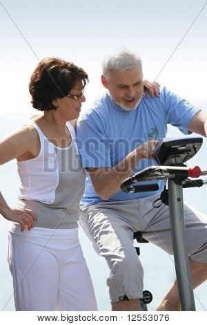Portrait of a senior woman next to a senior man making exercise bike