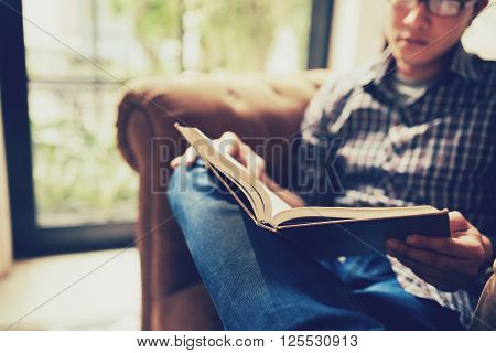 Man sitting in chair and reading novel, selective focus
