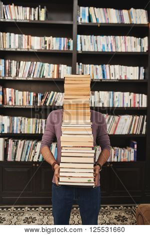 Man carrying big stack of books in library