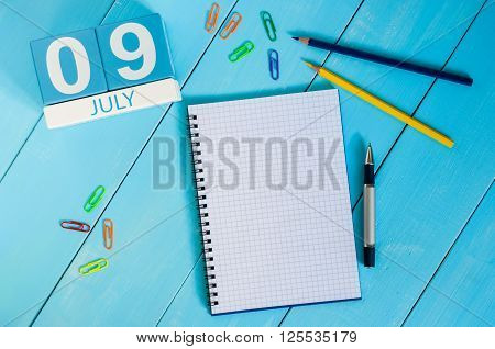 July 9th. Image of july 9 wooden color calendar on blue background. Summer day. Empty space for text.