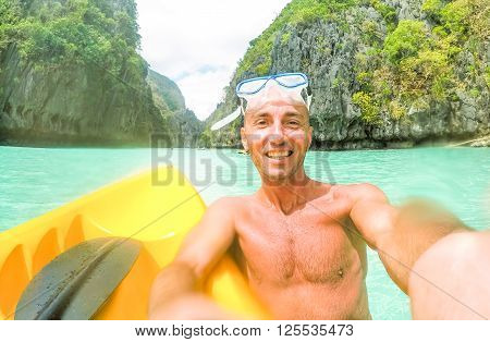 Tourist man having fun taking selfie on kayak at Big Lagoon in El Nido Palawan - Cheerful bather male swimming at Philippines islands - Concept of tropical travel with drops of water on the lens