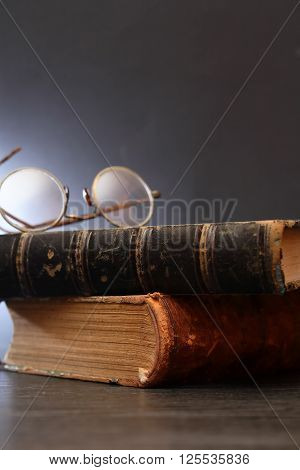 Vintage still life with spectacles on stack of old book on dark background