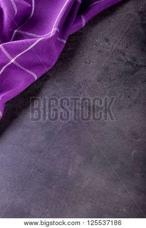 Top view of checkered kitchen purple tablecloth on concrete - stone - marble - wooden background. Free space for your text or products.