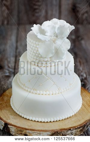 Three layered wedding cake covered with white fondant, decorated with beads and hand-made flower on top