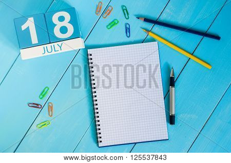 July 18th. Image of July 18 wooden color calendar on blue background. Summer day. Empty space for text.