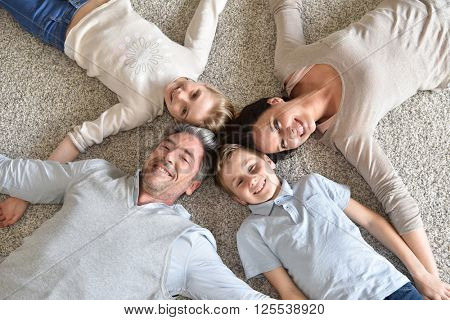 Upper view of family of 4 laying on carpet