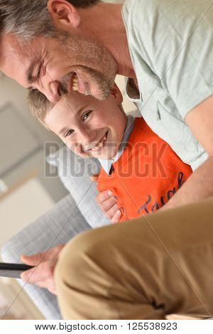 Cheerful boy playing on digital tablet with daddy