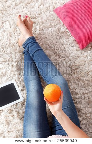 Woman on diet holding a whole orange