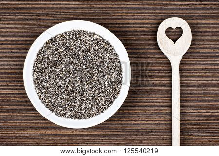 Chia seeds on white porcelain plate with cooking wooden spoon (cut heart shape) on wood background table.