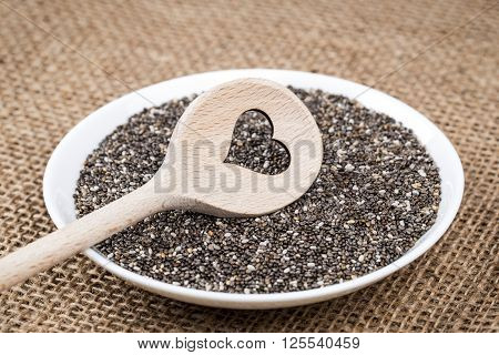 Chia seeds on white porcelain plate with cooking wooden spoon (cut heart shape) on burlap background.