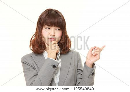 young Japanese businesswoman doubting on white background