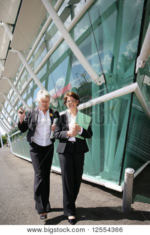 Portrait of senior women in suit walking with laptop computer and documents