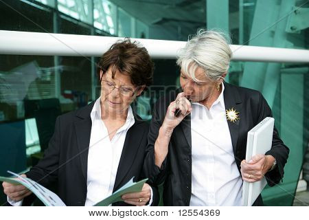 Portrait of senior women in suit with laptop computer and documents