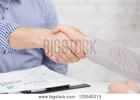 Two business people shaking hands indoors. Man and woman are business partners, who agreed to sign contract or agreement.