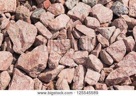 Macro of pink crushed stones (angular rock) used for road construction