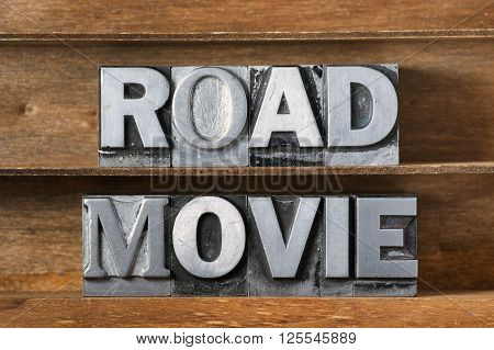 road movie phrase made from metallic letterpress type on wooden tray