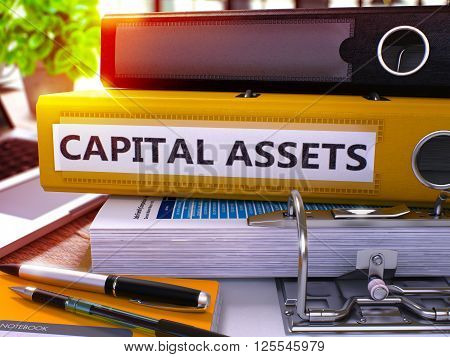 Yellow Ring Binder with Inscription Capital Assets on Background of Working Table with Office Supplies and Laptop. Capital Assets Business Concept on Blurred Background. 3D Render.