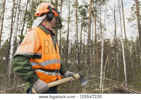 Lumberjack with an axe in the hands of the forest backdrop. One worker in special clothes in the foreground.