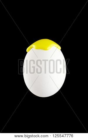 White egg drenched in yellow colors on a black background
