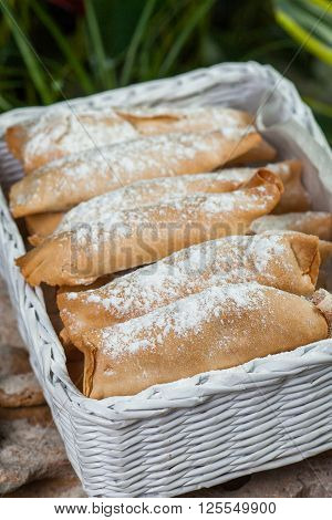 baking of unleavened dough with sweet filling, sprinkled with powdered, lined in a wicker basket