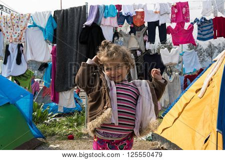 EIDOMENI, GREECE - MARCH 17, 2015: A little girl smiles outside her tent on March 17, 2015 in the refugee camp of Eidomeni, Greece. For several weeks more than 10.000 refugees and immigrants wait here for the borders to open.