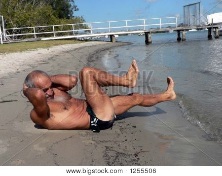 Man Doing Situps On Beach