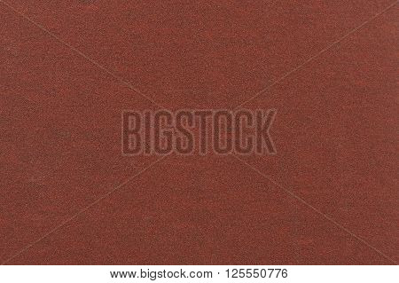 A macro shot of fine brown sandpaper