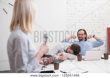 Long and boring presentation of business woman in office. Tired and exhausted men listening to her and sleeping.