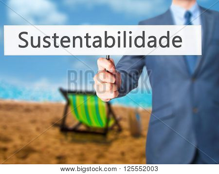 Sustentabilidade (in Portuguese - Sustainability) - Businessman Hand Holding Sign