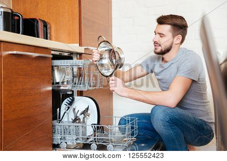 Serious bearded young man washing dishes using dishwasher on the kitchen