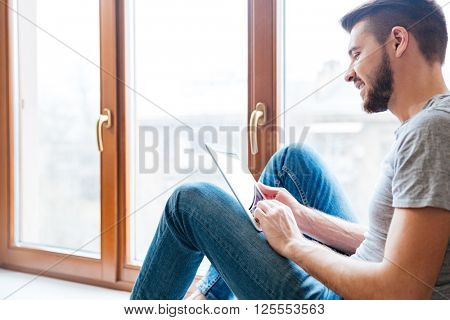 Happy handsome young man sitting on window sill and using tablet