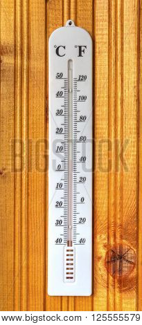 Classic thermometer on wooden board close up