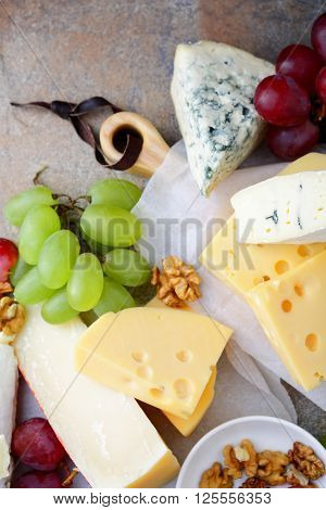 Set Of Delicatessen Cheeses With Grapes And Walnuts On The Slate Background