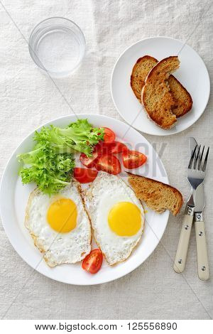 Fried Eggs With Lettuce, Tomato, Bread And Water Glass On A Linen Tablecloth
