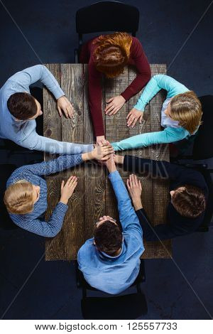 Top view creative photo of business people sitting at dark wooden vintage table. Business people having meeting. Concept for successful teamwork