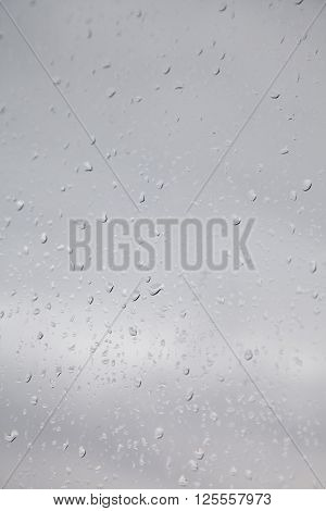 raindrops on a window with grey cloudy sky.