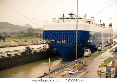 Panama City Panama - August 31 2015: Huge cargo ship enters the transit point of Miraflores Locks in Panama Canal on a rainy day. Central America