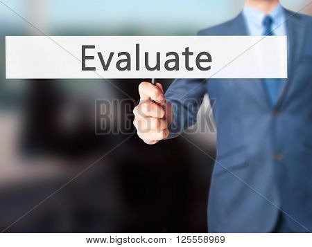Evaluate - Businessman Hand Holding Sign