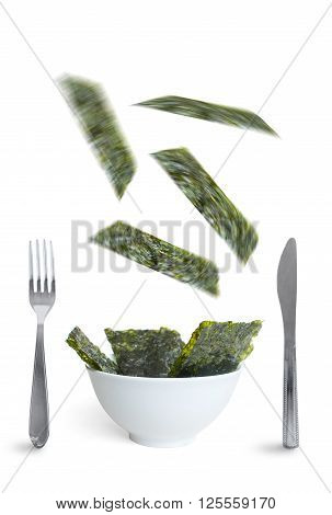 Seaweed slices falling into a bowl over a white background a superfood that is high in vitamin c iron and promotes healthy bacteria in the gut