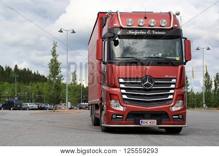 FORSSA FINLAND - JUNE 21 2015: Red Mercedes-Benz cargo truck drives through asphalt yard of a truck stop. In February 2016 Mercedes-Benz Trucks has the market share of 184 per cent in Finland.