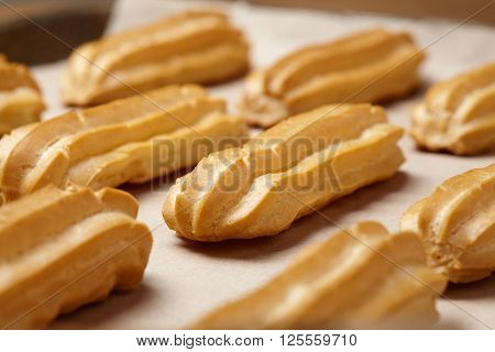 Homemade eclairs traditional french profiterole dessert on baking sheet background. Close up view