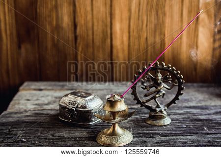 Incense in symbol and Beautiful Candlestick. Luxurious antique gold service. Spiritual religious Hindu concept. Eastern Still life on a blurred Background