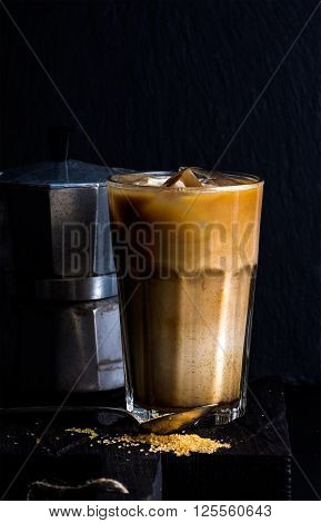 Iced coffee with milk in a tall glass, moka pot, black background, selective focus